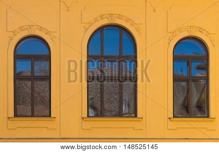 Ornate yellow facade of an old building with three windows with archs reflecting a blue sky and a roof a the oposite building.
