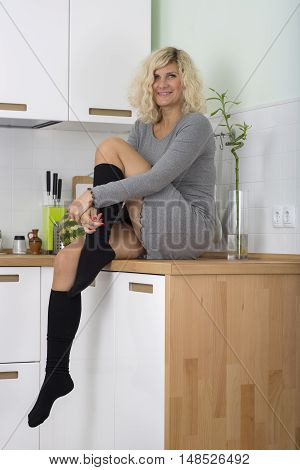 Blonde girl with curly hair is seating on the kitchen table