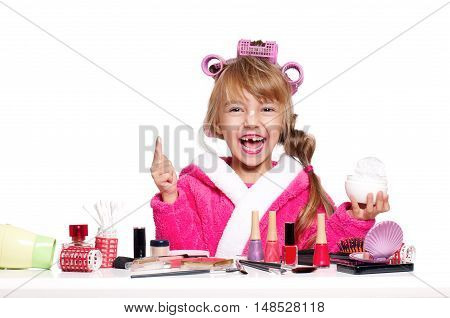 Adorable little girl playing with mommy's make up. Fashion little child applying cream for face, isolated on white background. Kid learning to be a modern woman.