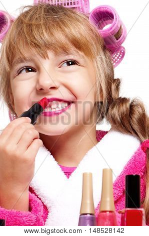 Adorable little girl playing with mommy's make up. Happy kid painting her lips. Fashion little child applying make-up on white background.