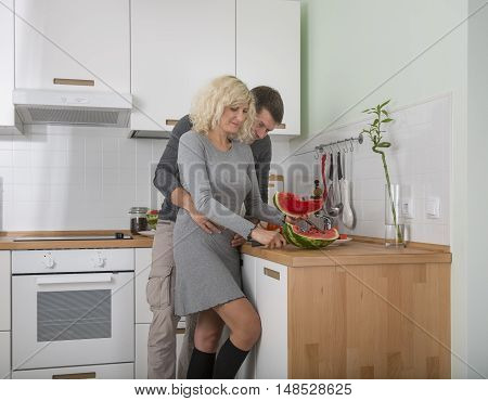 Beautiful couple is eating waterelon on the kitchen