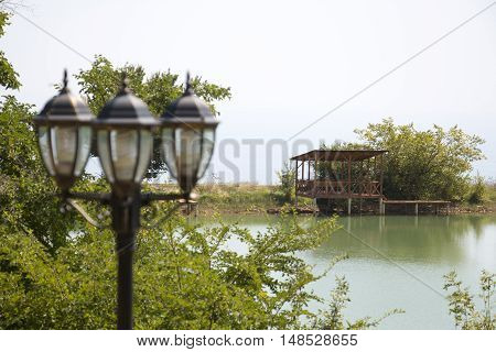 Gazebo on the shore of the pond in the background of a lamppost