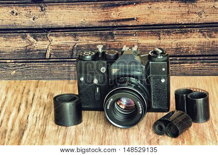 Old retro photo camera and film negative strip on wooden table against timber wall.Retro style toned image.