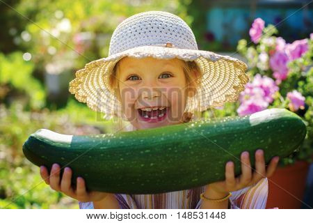 Little girl is delighted with his zucchini