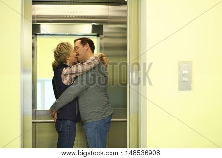 Man with a mustache and woman hugging and kissing in the elevator
