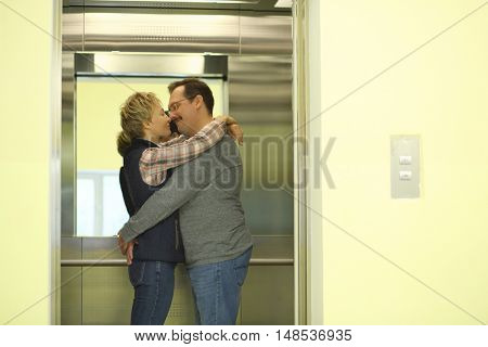 A man with a mustache and a woman hugging in an elevator