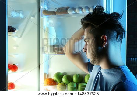 Man choosing food in kitchen. Hunger concept