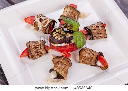 Grilled eggplant rolls with vegetables and sauce on white plate