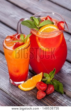 orange and strawberry iced tea on wood background