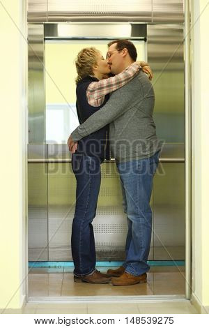 Man and woman hugging and kissing in the elevator