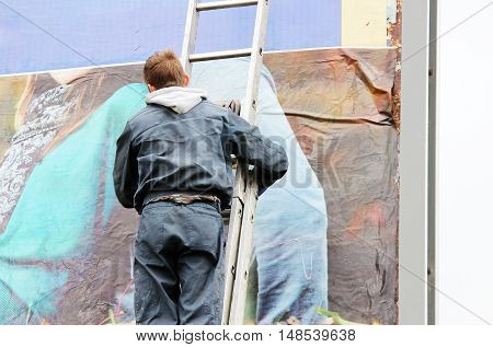 young worker glues a poster with a picture of a autumn girl on a billboard.