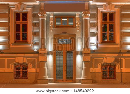 Several windows in a row and door on night illuminated facade of urban office building front view St. Petersburg Russia