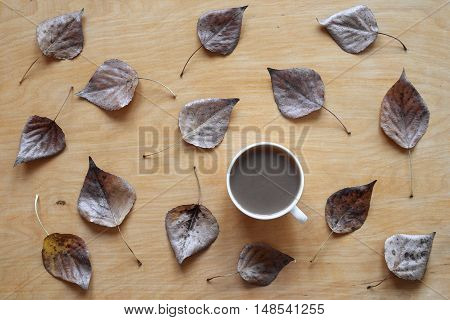A cup of black coffee and autumn dried leaves on a wooden background. Shot from above.