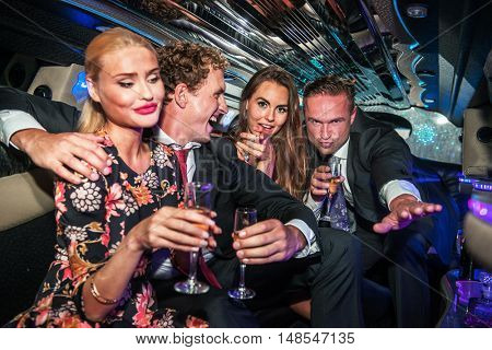 Group of friendshaving fun in a limousine, during a night out, enjoying a glass of champagne, and being