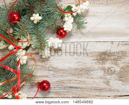 Christmas or New Year background: fur-tree branches, colorful glass balls, decoration and glittering stars on white wood