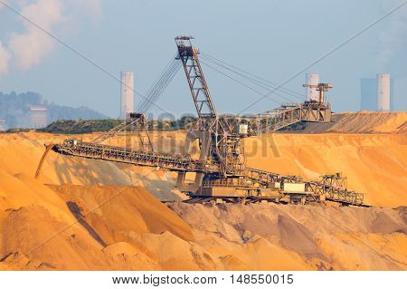 Mining machinery in a brown coal open pit mine. In the background are the power plants.