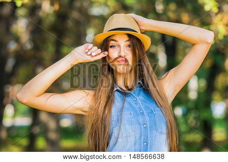 Cool young blonde Caucasian woman making mustache with her hair. Beautiful teenage girl making funny faces using her long blonde hair to make mustaches. Natural light, mild retouch.