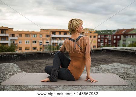 Woman is  practicing yoga on the roof,Ardha Matsyendrasana