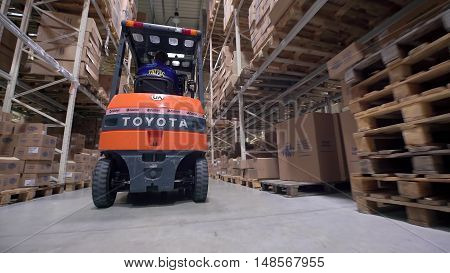 LUBLIN, POLAND - APRIL 21, 2016: Logistics business and shipping facility with manual worker operating forklift to move boxes and goods, man working in warehouse, worker in industry.