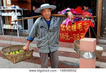 Luo Dai China - October 13 2007: Street vendor carrying baskets filled with oranges suspended from a shoulder yoke