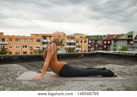 Beautiful woman practicing yoga on the roof,Bhujangasana/Cobra Pose