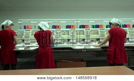 LUBLIN, POLAND - APRIL 21, 2016: Cropped Side View of Hands Stitching Piece of Fabric on Automatic Sewing Machine..
