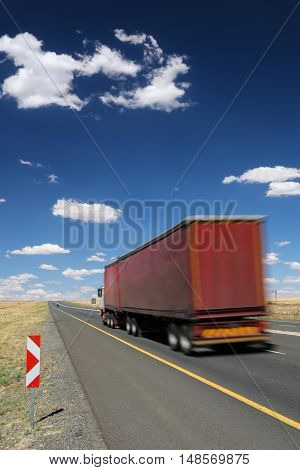 Big transporter truck travelling along the highway at speed