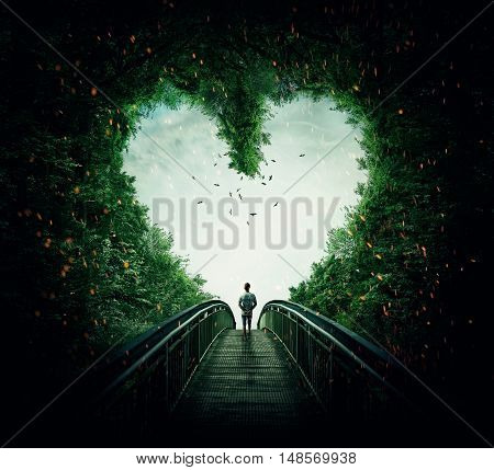 Boy walking on a bridge through the heart shape woods following the light. Follow your heart concept