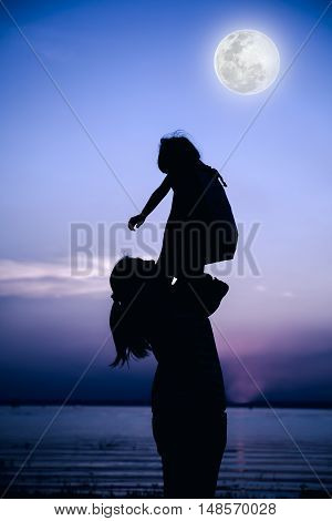 Silhouette Of Mother And Child Enjoying The View At Riverside.  Cool Colors.