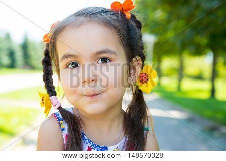 Adorable little kazakh asian child girl on summer green nature background.