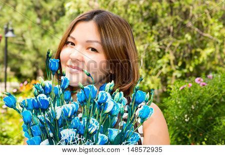 Portrait of the asian Kazakh young beautiful smiling woman and flowers outdoor