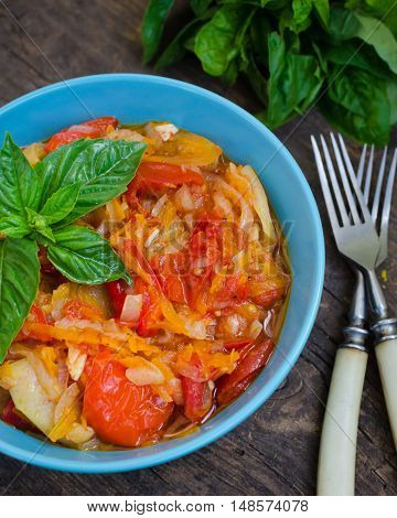 Italian peperonata: roasted bell pepper with onion and basil in a bowl on old wooden background. Pepper lecho stew ragout. Peperonata - traditional dish of italian cuisine. Italian cuisine concept.