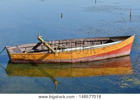 Anchored yellow rowboat and its reflection in the lake