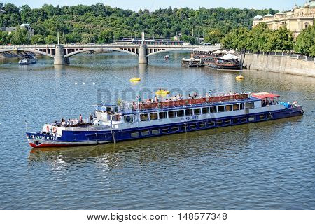 PRAGUE, CZECH REPUBLIC - JULY 3, 2014: View of the Vltava river with cruise tour boats from the Charles Bridge.The Charles Bridge is a famous historic bridge that crosses the Vltava river.