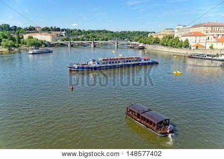 View of the Vltava river with cruise tour boats from the Charles Bridge. The Charles Bridge is a famous historic bridge that crosses the Vltava river in Prague Czech Republic.