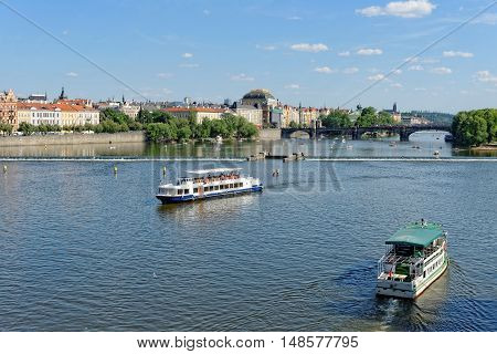 View of the Vltava river with cruise tour boats from the Charles Bridge. The National Theatre and the Legion bridge are seen. Prague Czech Republic.