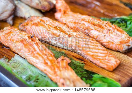Fillet of salmon. Fresh and beautiful salmon fillet on a wooden table. Delicious fish meat. Grilled salmon on wooden cutting board.
