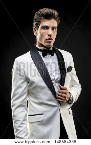 Boss, elegant man in a white suit tuxedo with bow tie around his neck