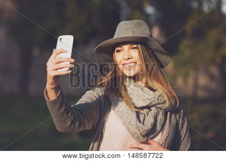 Modern young beautiful woman taking a selfie in park in autumn. Teenage girl in gray fedora hat, gray scarf and sweater photographing herself outdoors in fall. Matte filter applied, natural light.