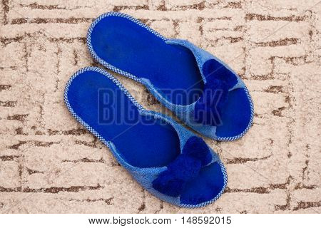 Blue slippers on carpet. Welcome home concept.