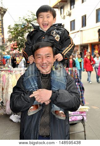 Pengzhou China - December 11 2009: Happy little Chinese boy sitting atop his father's shoulders on Li Ren Jie Street