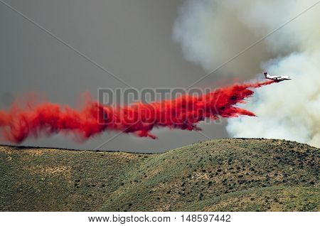 White Aircraft Dropping Fire Retardant as it Battles the Raging Wildfire poster