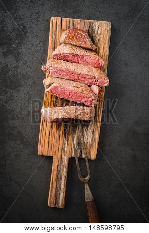Sous vide cooked and seared fillet steak on rustic wooden board