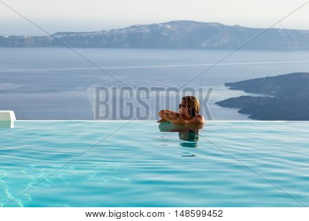 Man on the edge of an infinity pool watching the scenery