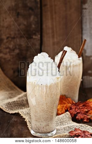 Pumpkin Spice Iced Coffee with whipped cream and cinnamon against a rustic background. Shallow depth of field with selective focus on Latte in foreground.
