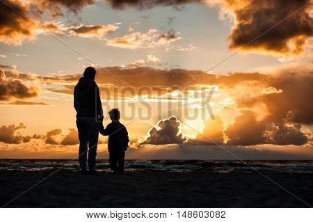 A woman holding a child's hand during sunset