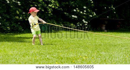 Child drags hose with water in garden