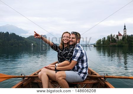 Young Couple Of Tourists On Wooden Boat On The Lake Bled, Slovenia.