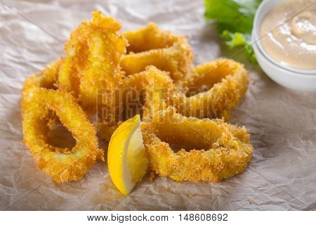 Fried squid rings with lemon and sauce