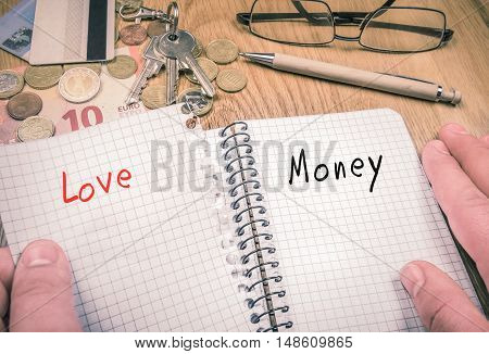 Choosing money over love concept - Man's hands ripping a sheet with the word love remaining the page with the word money in the notebook. There are financial elements and pen in the background.